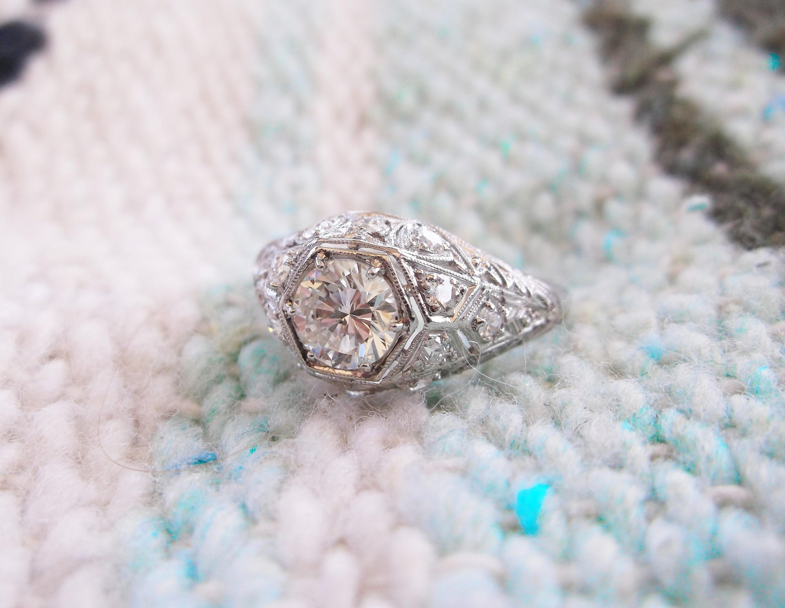 Beautiful 0.86 carat round brilliant cut diamond set in an Art Deco diamond and platinum mounting.