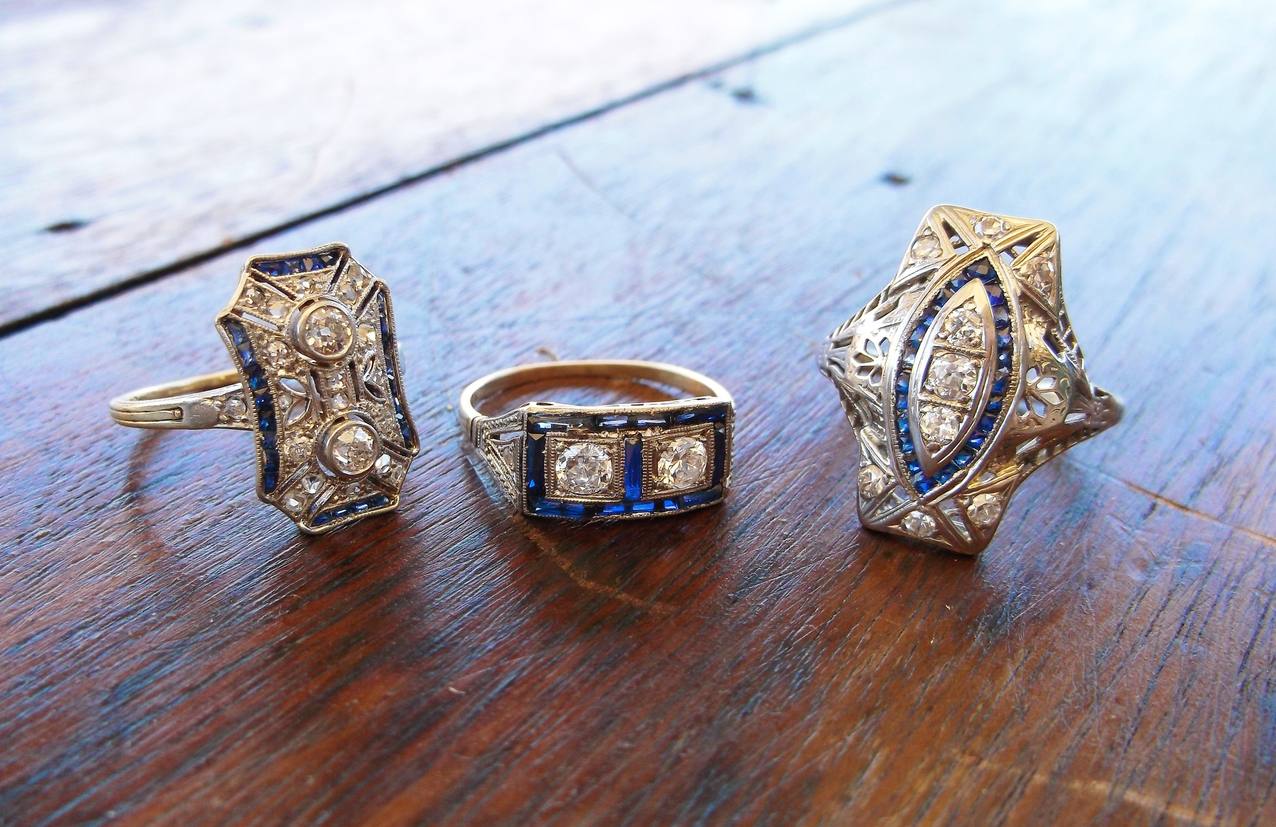 Three lovely Edwardian and Art Deco diamond rings with beautiful sapphire details. From left to right: *SOLD - Edwardian era, platinum topped gold, diamond and sapphire ring with 0.40 carats total weight in diamonds with 0.45 carats total weight in diamonds. *SOLD - Edwardian era, platinum topped gold, diamond and sapphire ring with two 0.15 carat Old European cut diamonds in the center. *SOLD - Art Deco, platinum and white gold, diamond and sapphire ring with 0.40 carats total weight in diam...onds.