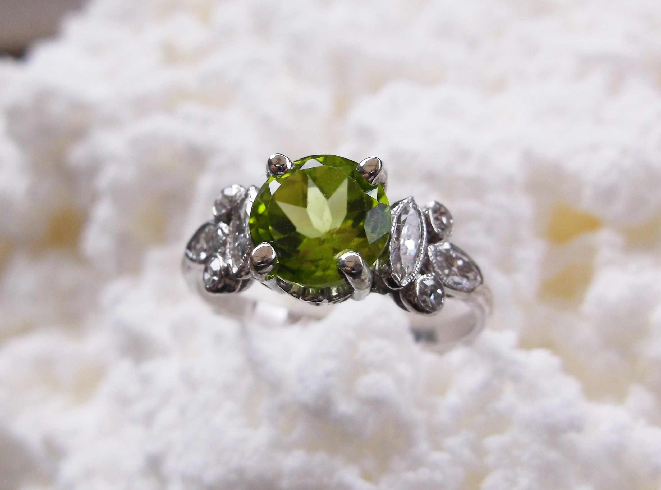 SOLD - Electric green 1.36 carat peridot with 0.40 carats total weight in diamonds set in platinum.