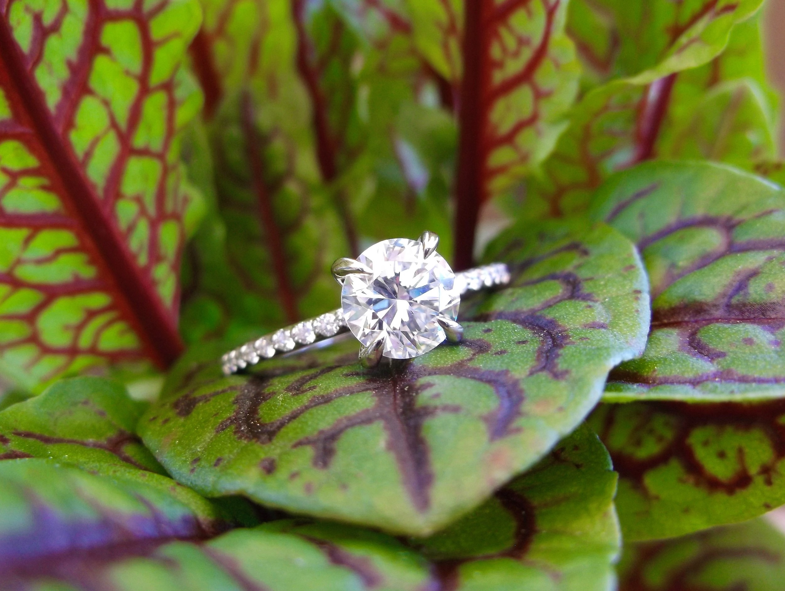 Pristine 1.12 carat round transitional cut diamond set in a dainty diamond and white gold mounting.
