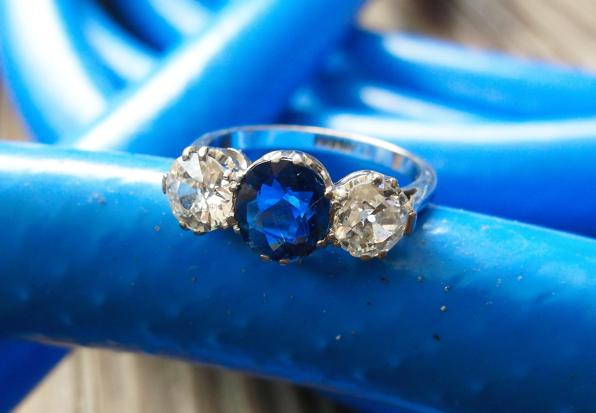 SOLD - Boldly beautiful 1920's diamond and sapphire ring with a 1.24 carat blue sapphire in the center and a 0.55 carat Old Mine cut diamond on each side.