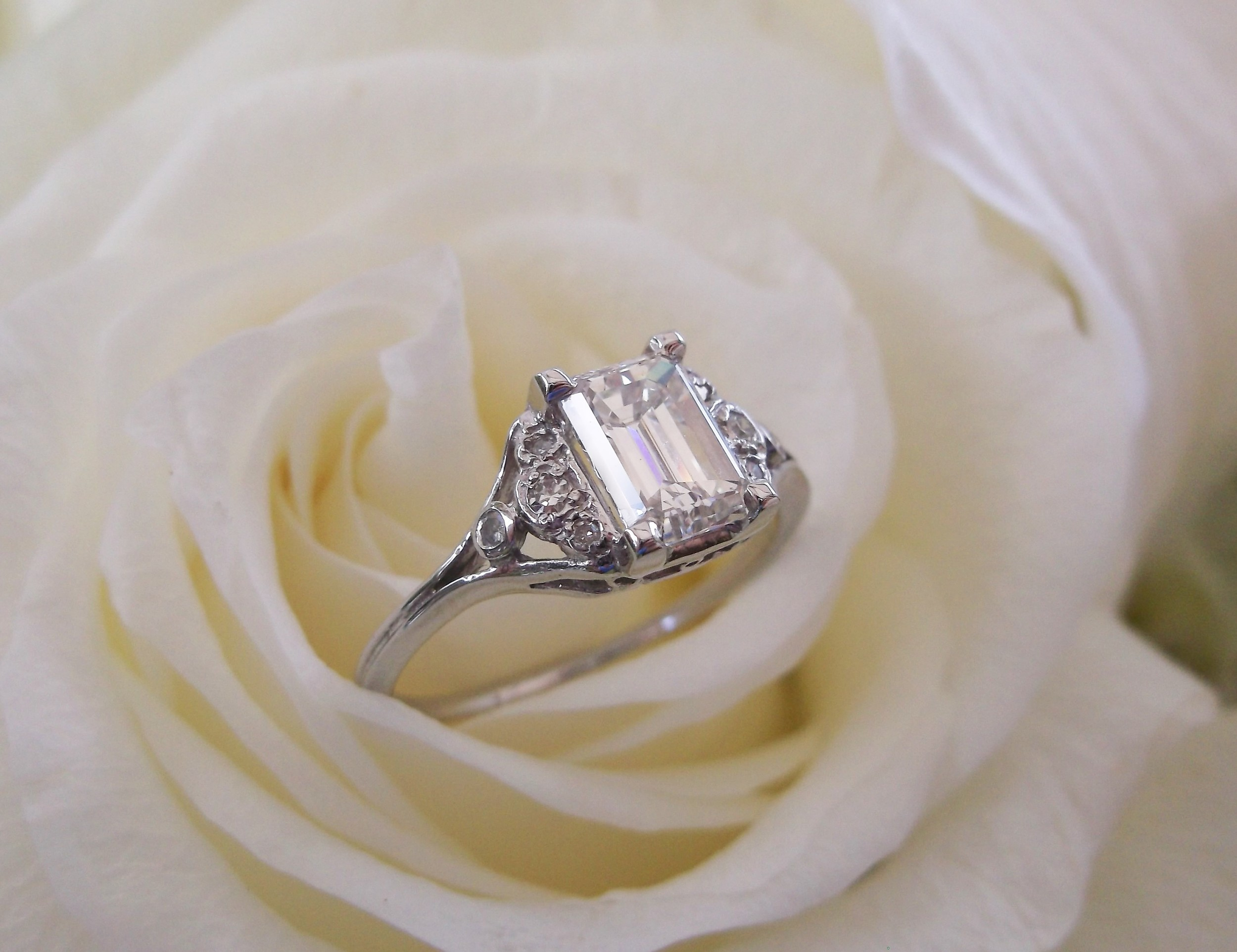 SOLD - Sophisticated 1.07 carat emerald cut diamond set in white gold with diamond detail on the sides from the 1920's.