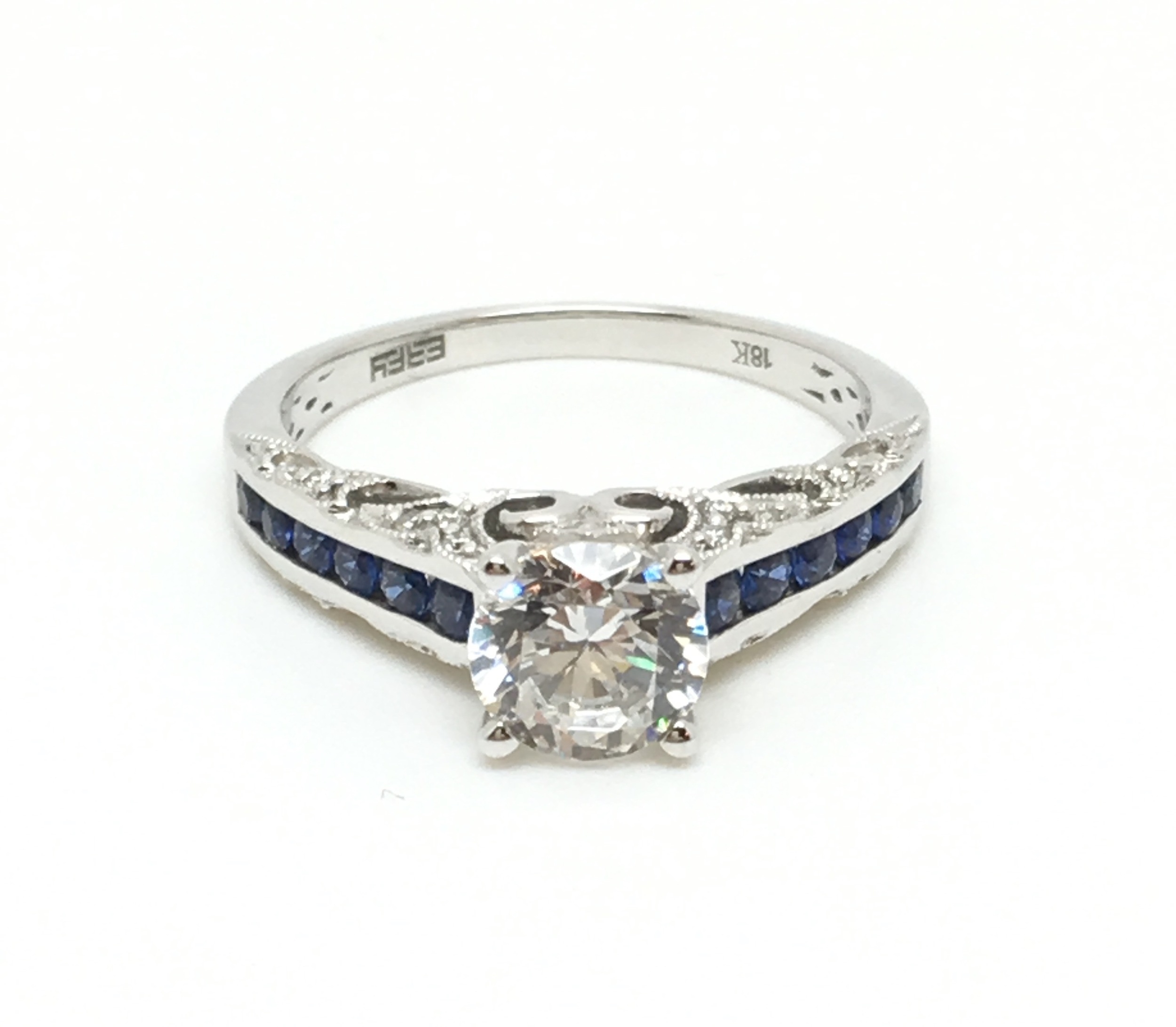 Does your diamond need an upgraded look? This gorgeous 18K white gold and blue sapphire mounting is available in our sale! (Pictured here with a CZ in the center to help visualize what your stone will look like set in the setting. The setting will accommodate a one carat center diamond. )