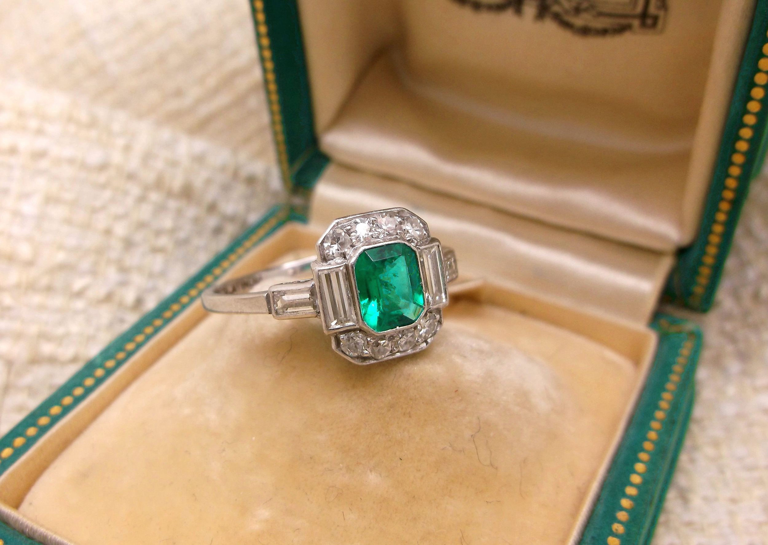 SOLD - Gorgeous Art Deco ring, featuring a center 0.50 carat emerald, surrounded by 0.70 carats total weight in diamonds, all set in platinum.
