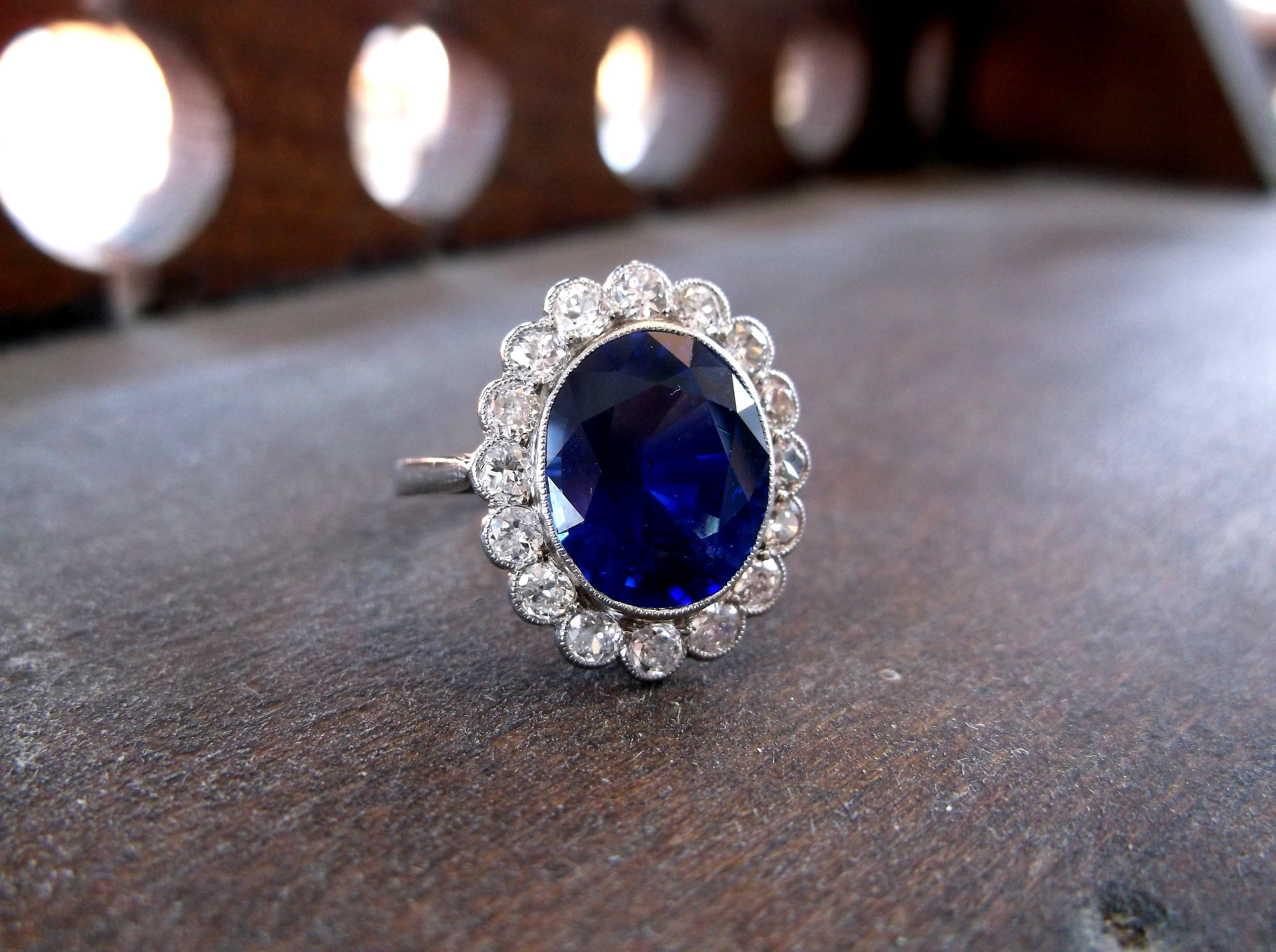 SOLD - Vibrant and captivating 4.50 carat oval blue sapphire, surrounded by 0.75 carats total weight in Old Mine diamonds.