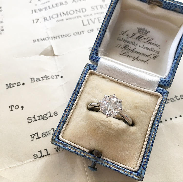 Meet Mrs. Barker.  Why the name, you ask?  This 2.00 carat Old European cut beauty was purchased in 1940, by Mrs. Barker in Liverpool, England. Here, the ring is pictured with the original receipt in the original box with the original care card, addressed to Mrs. Barker. During that time, Liverpool was in the thick of World War II. It was targeted by the Germans - and badly hit - because it was a port town. Although the heaviest bombings occurred during the later part of the year, as well as the following year, there is no telling what this ring, and Mrs. Barker endured.  Shop this ring  HERE