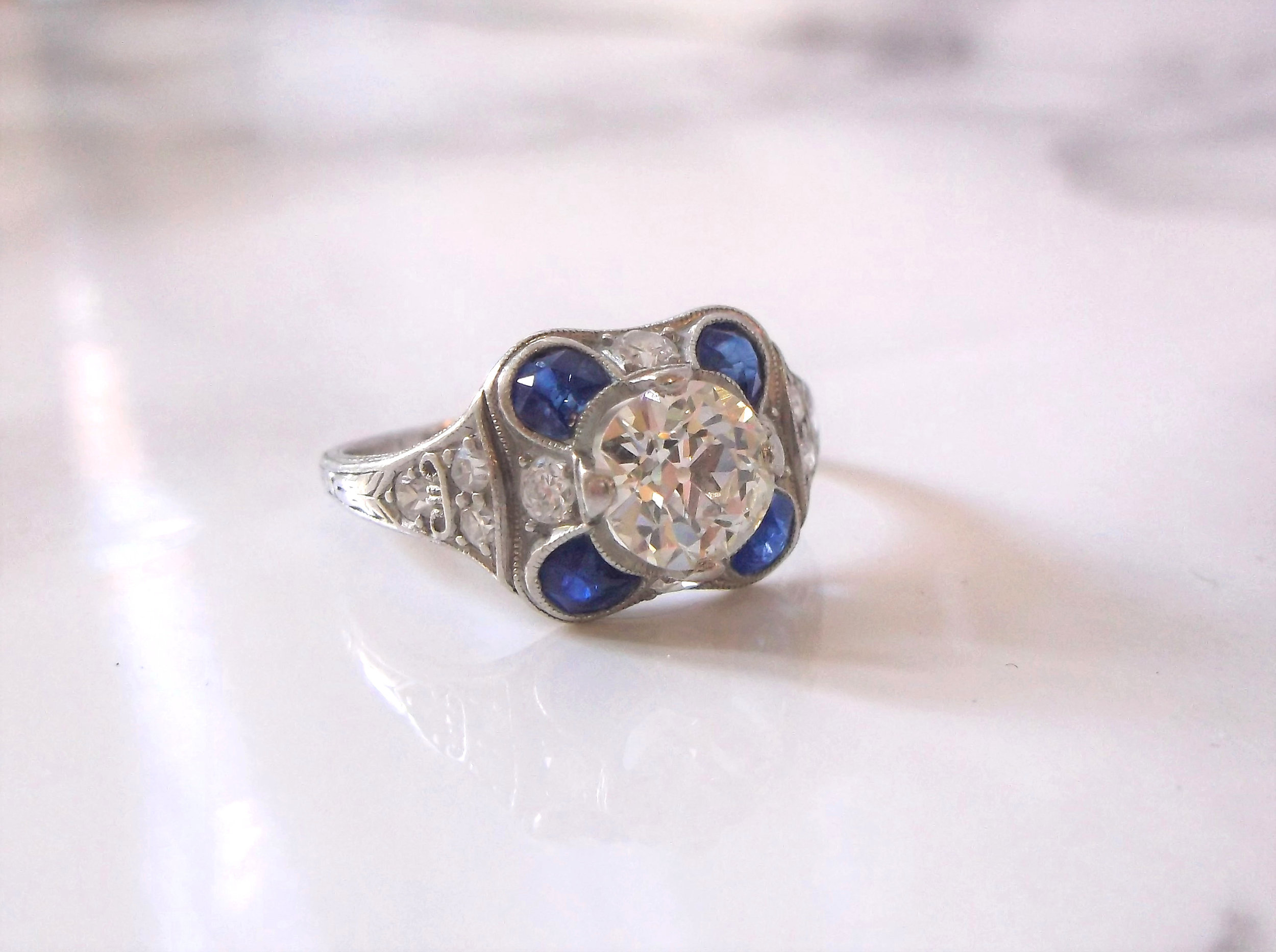 SOLD - What's not to love about this fabulous 1920's Old European cut diamond and sapphire ring?! The ring features a center 1.15 carat Old European cut diamond, surrounded by 0.50 carats in sapphires and 0.25 carats in accent diamonds, all set in platinum.  Shop this ring  HERE