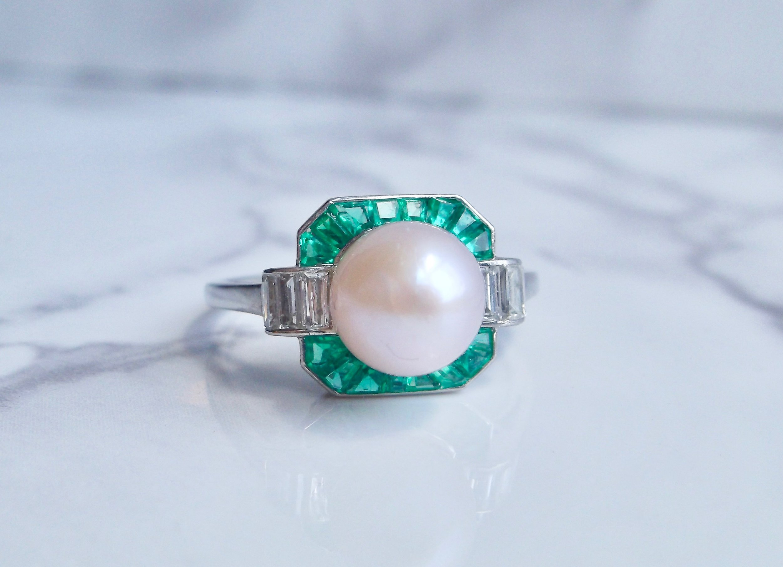 Fabulous 1920's pearl, emerald and diamond ring set in platinum. The ring features a beautiful white pearl with rose overtone, surround by approximately 1.00 carats in emeralds with step cut diamond details on the side. Southern elegance meets Art Deco style! Shop this ring  HERE