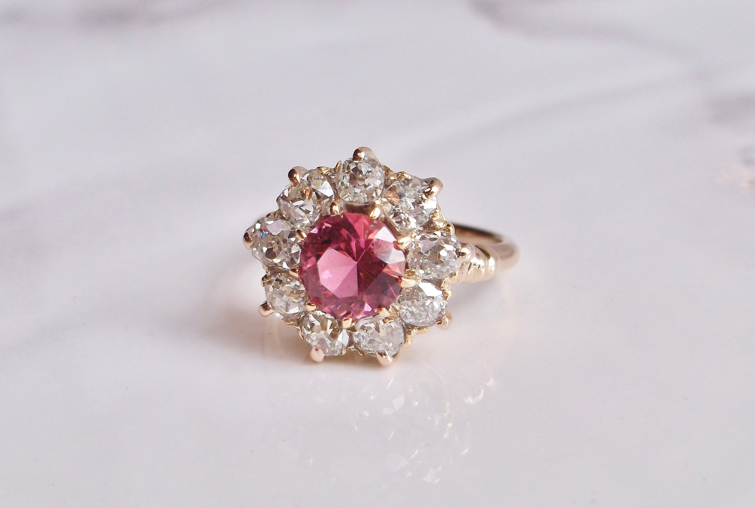 Add a pop of pink to your wardrobe with this lovely pink tourmaline, Old Mine cut diamond and yellow gold ring!  The ring features a center round brilliant cut pink tourmaline, surrounded by 2.00 carats in Old Mine cut diamonds.  Shop this beautiful ring  HERE