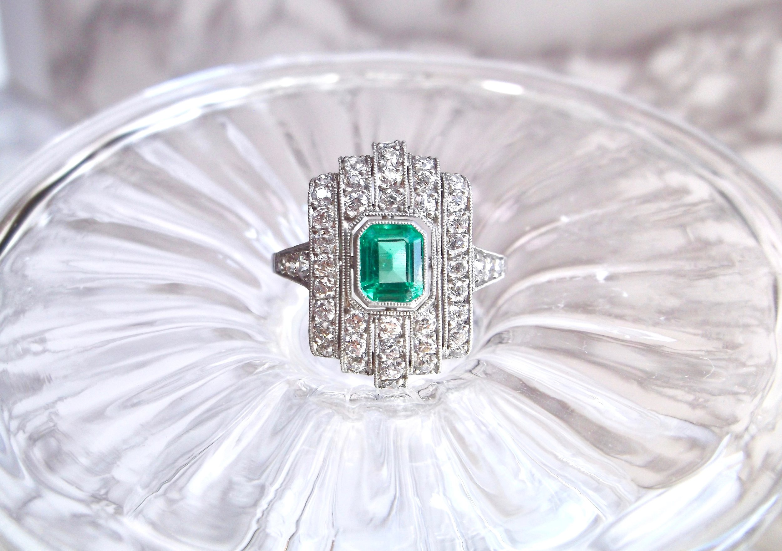 The Art Deco beauties keep rolling in! This gorgeous emerald, diamond and platinum ring features a center 0.65 carat step cut emerald, surrounded by 1.00 carats in Old Mine cut diamonds with gorgeous filigree details underneath!  See all the angles  HERE