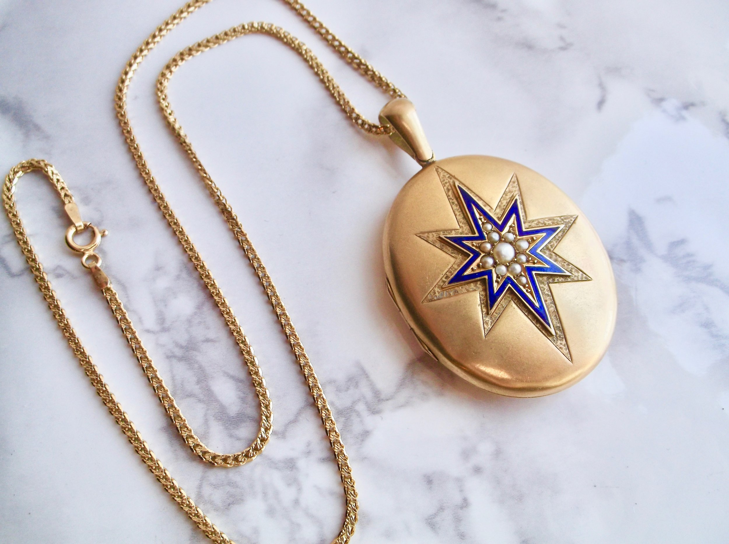 Stellar Victorian era locket featuring blue enamel, seed pearl and engraving details.  The perfect piece to keep your loved ones close to your heart! Shop this lovely necklace  HERE .