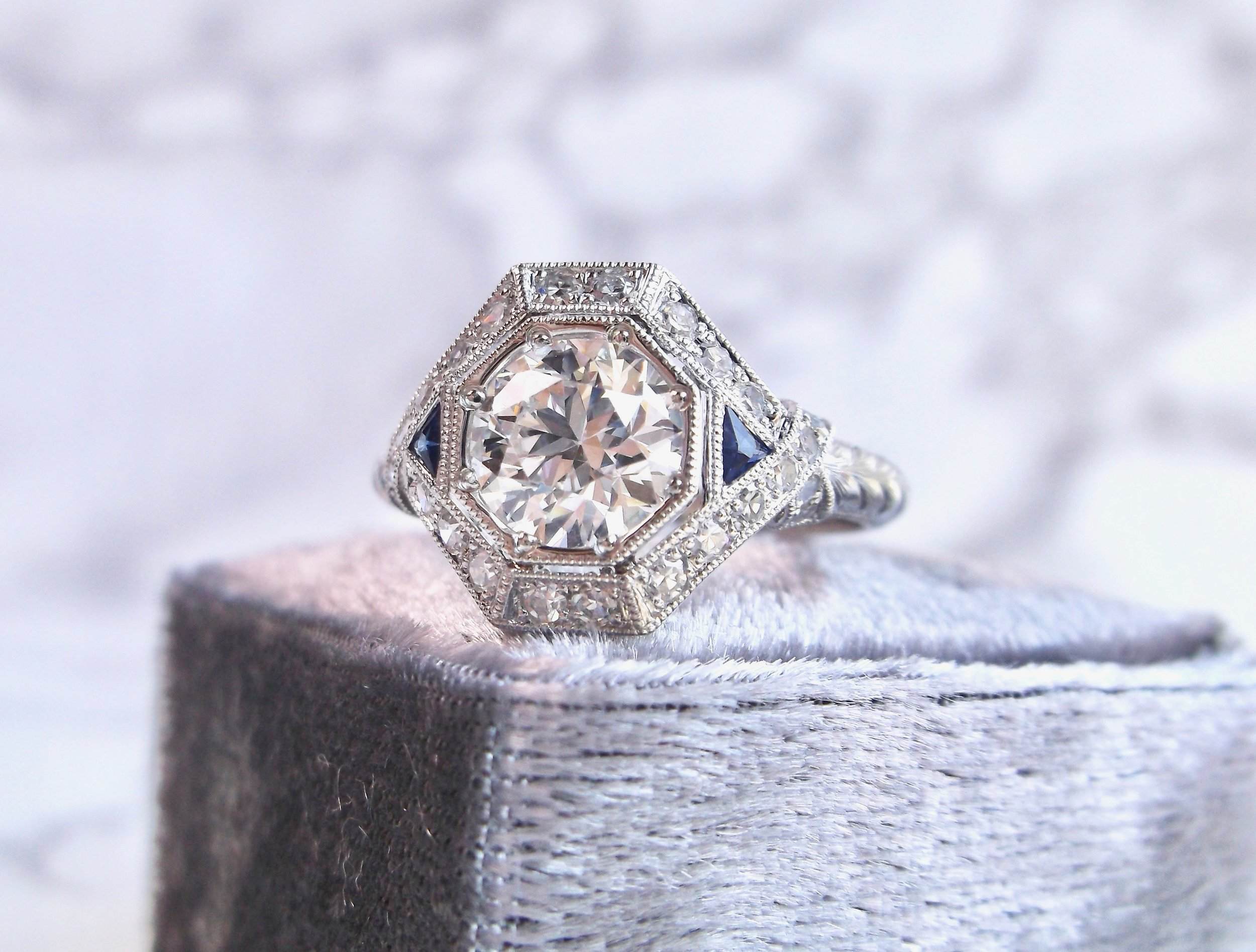 Phenomenal Old European cut diamond, sapphire and platinum ring.  The ring features a center 1.05 carat Old European cut diamond (VS1 clarity, F color), accented by 0.38 carats of single cut diamonds (VS1 clarity, G color) and 0.20 carats in sapphires with engraving details down the shank. Shop this stunner  HERE .