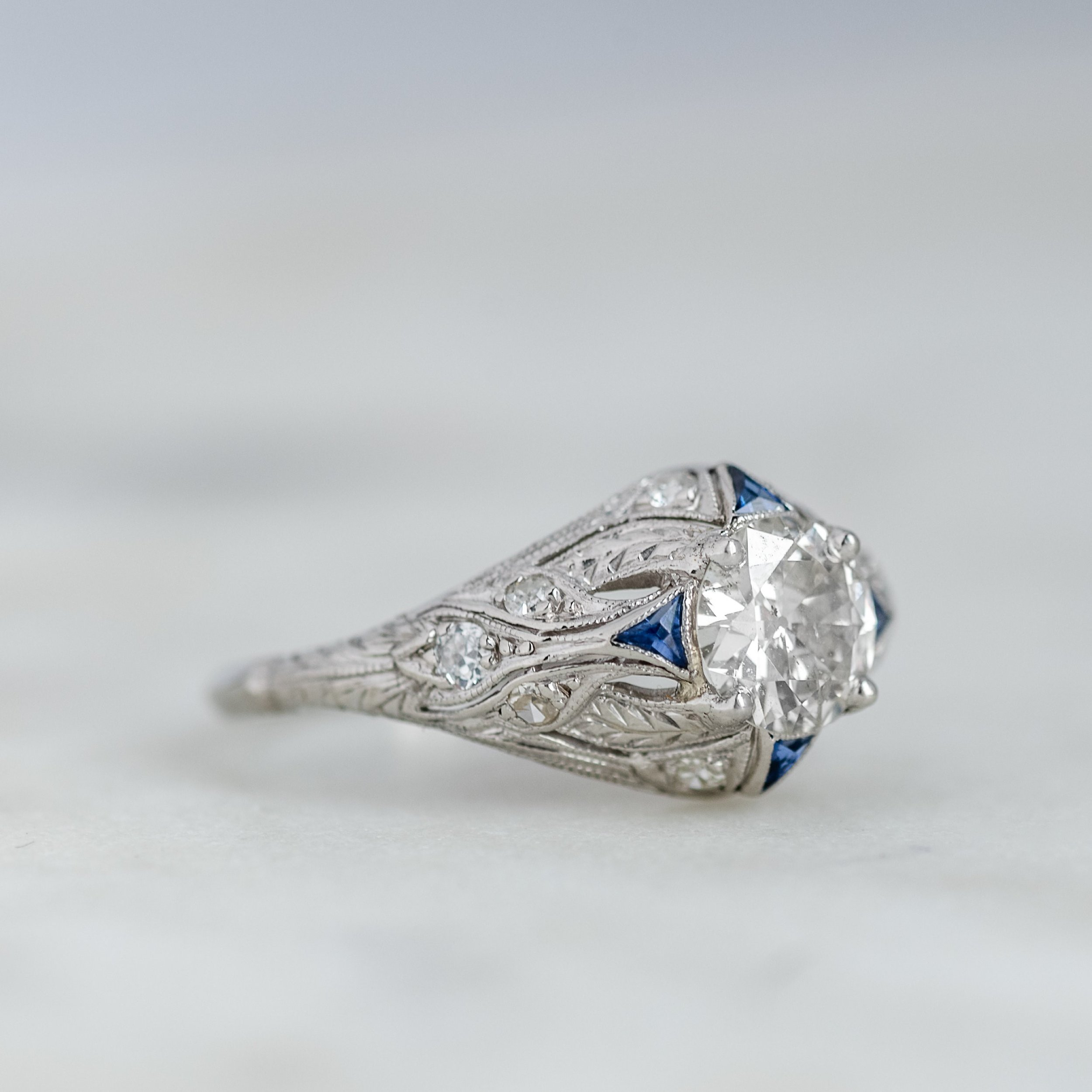 Jaw dropping Art Deco diamond ring featuring a center 1.10 carat Old European cut diamond, beautifully accented by blue sapphires. Shop this beauty  HERE .
