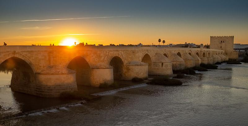 Golden sunset Roman Bridge across Guadalquivir River