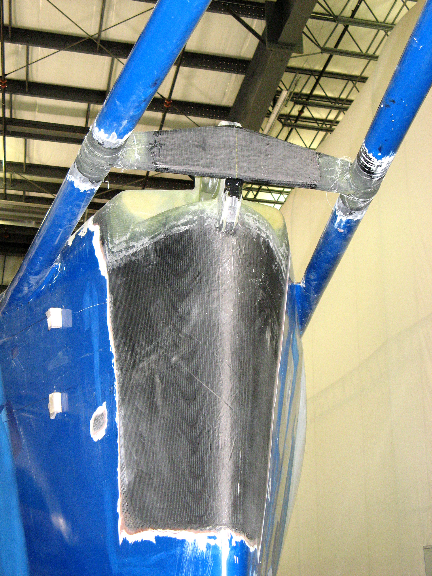 The repair required cutting away a section of              the bow to expose the solid carbon fiber centerline structure, repairing              and modifying the carbon fiber stem fitting, and then rebuilding,              fairing, and painting the stem.
