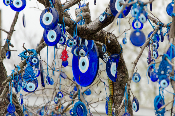 "I was told that it is believed that the Gods will take from you anyone/anything you give too much attention/love. Thus these ""evil eyes"" (everywhere in Turkey -- even in the roads-- are meant to take your gaze away from your loves so the Gods don't take away that which you love or admire."