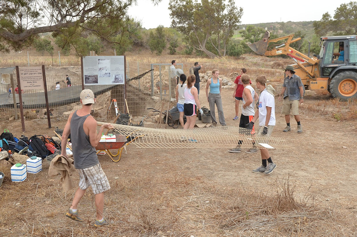 Volunteers and staff clean up Grid 51 at the start of the 2013 field season
