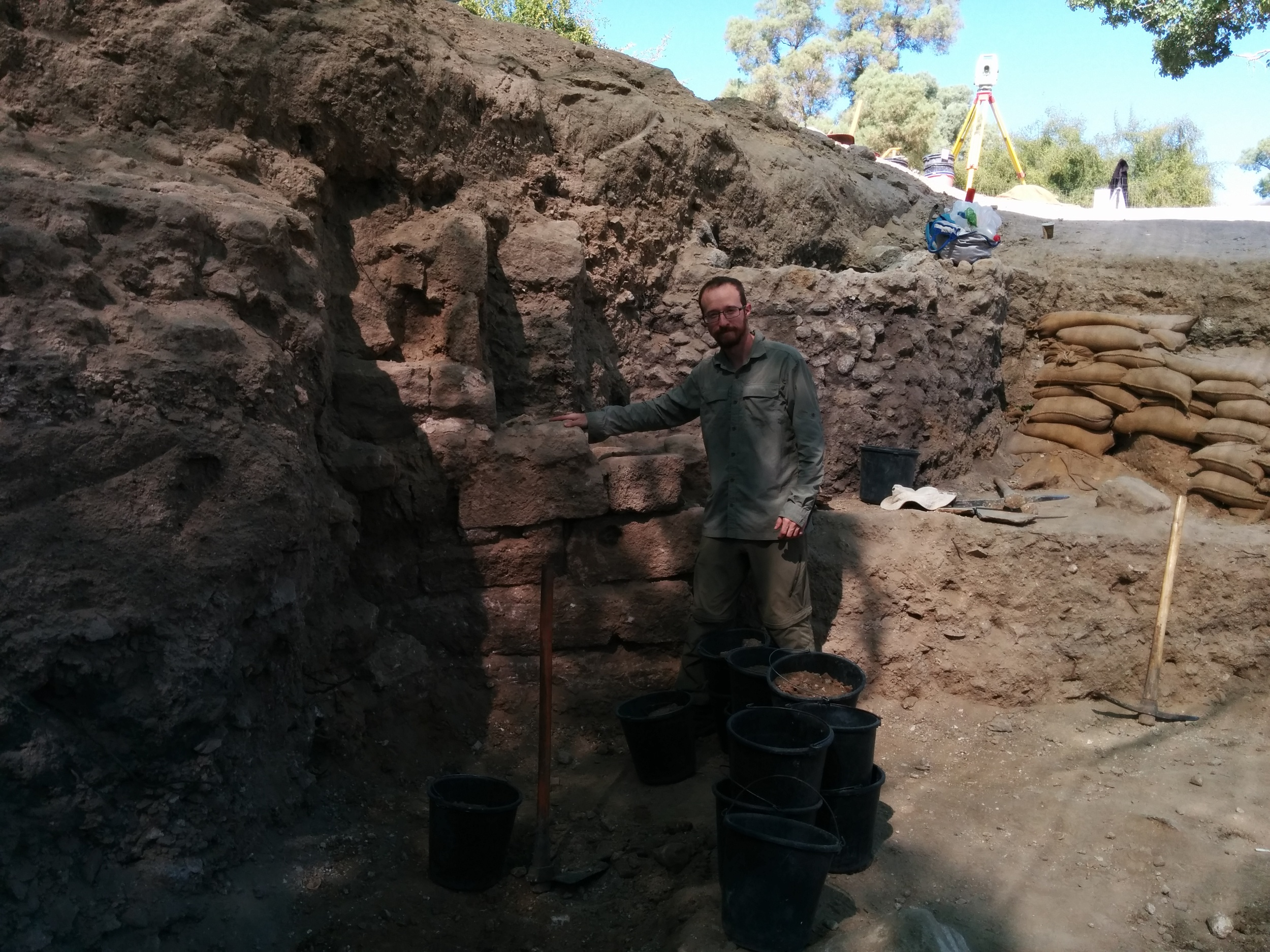 Ben standing next to a new wall/pier uncovered during excavation