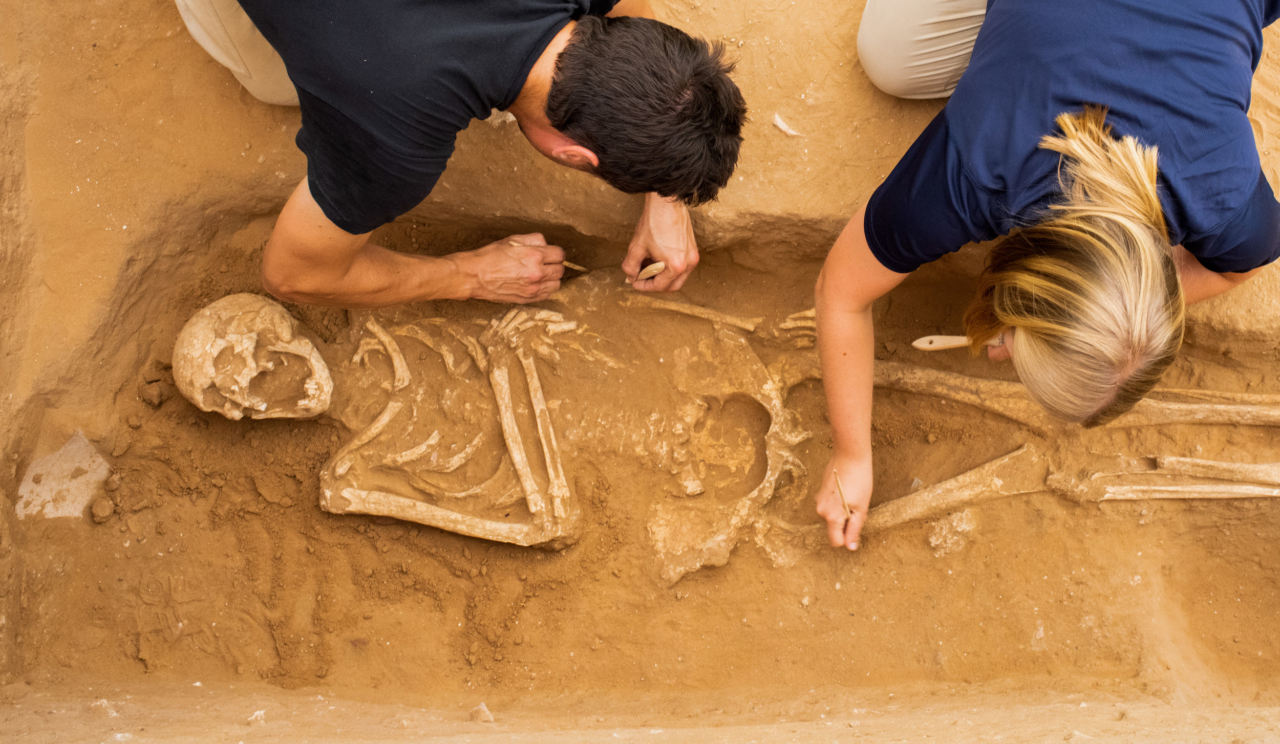 Adam Aja and Samantha Suppes excavate a 10th-9th century BC skeleton