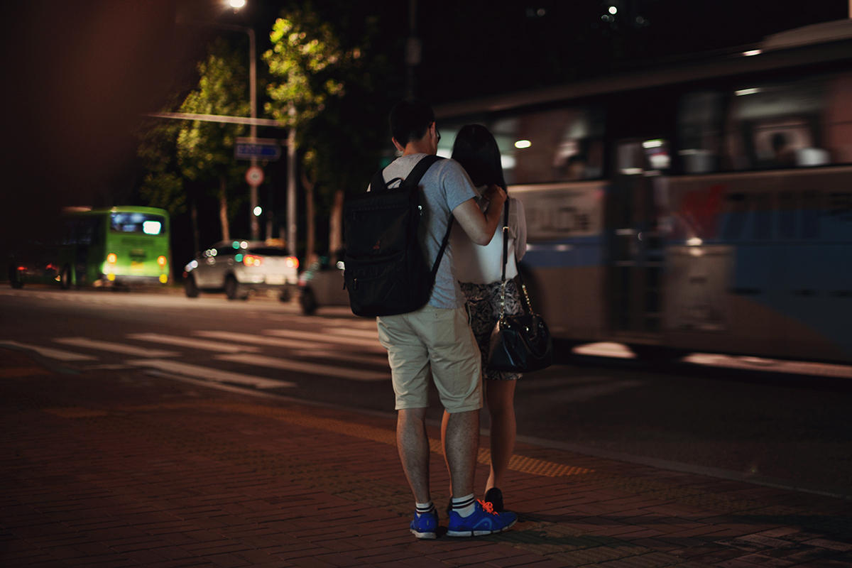 A boy massaging his girl at the bus stop