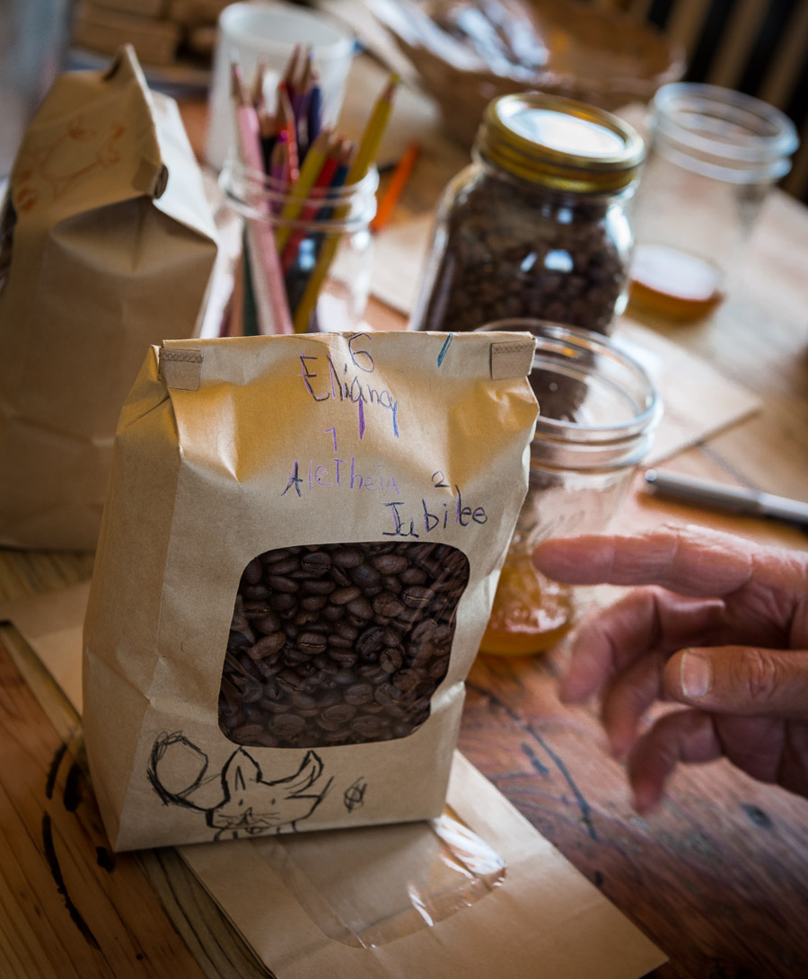 A guest at a public roasting points to a coffee bag neighborhood kids have decorated.
