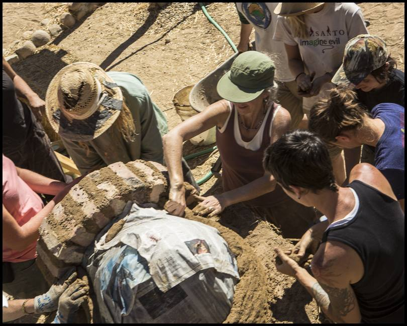 Participants begin building up the interior layer of the oven; the first layer is a dense clay-sand mixture, without straw.
