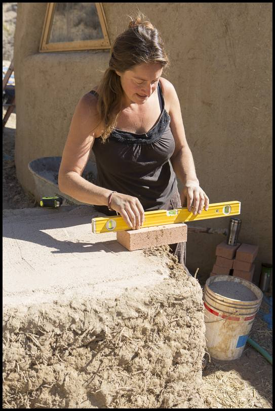 Sasha, the workshop instructor demonstrates setting the level for the bricks that will form the oven floor and hearth at the opening.