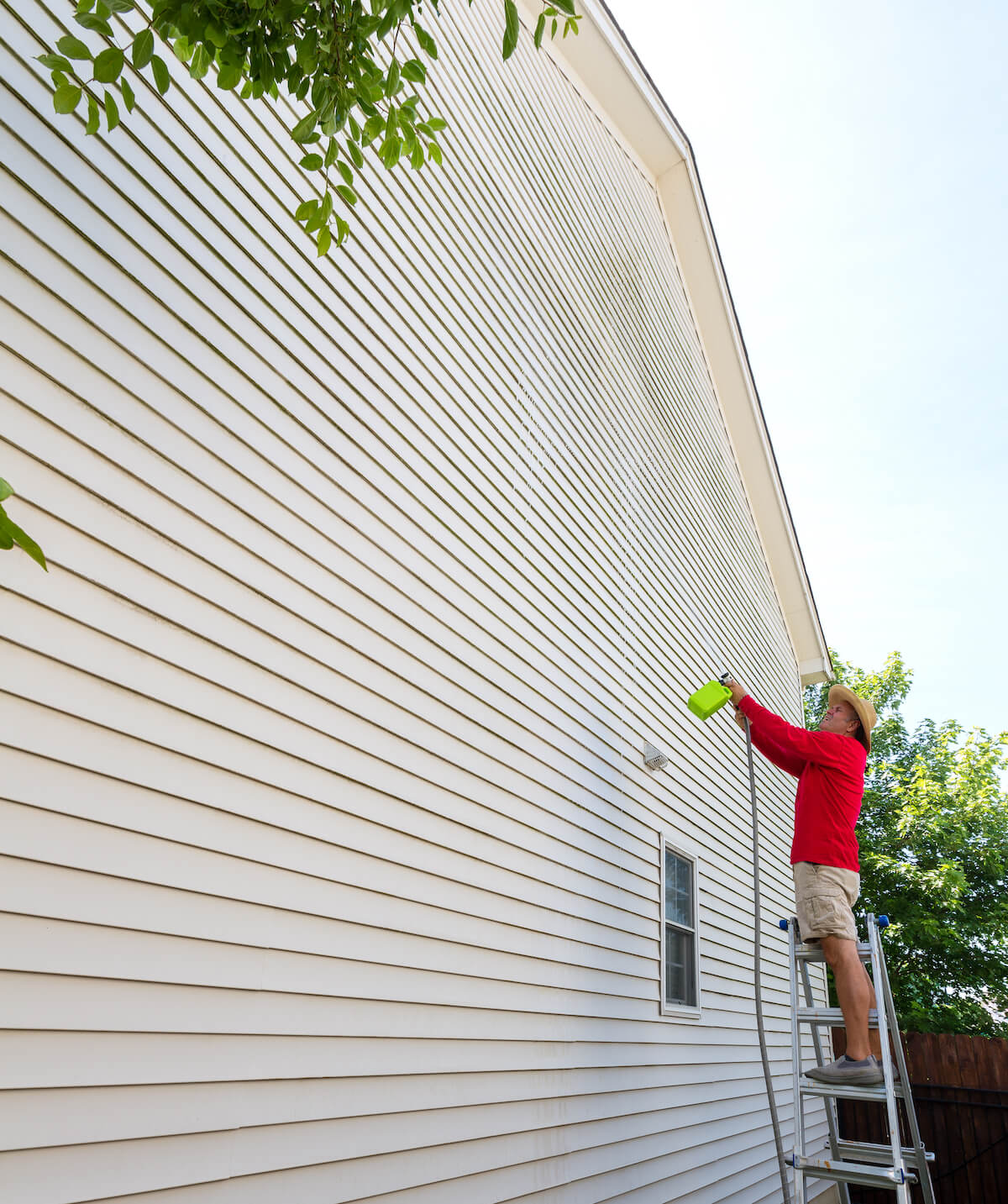 man spraying moss treatment onto siding of hillsboro home