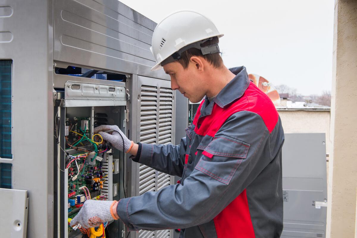 man servicing an HVAC air conditioning unit