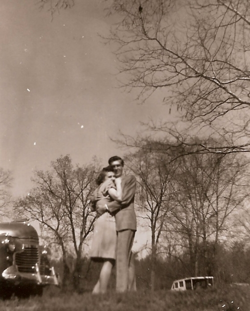 Mom (Marian Elizabeth Harbaugh) and Dad (Roscoe Wolfinger Boward).This photograph contains many things I love about photography - blur, light, dust, sepia, old cars, joy, and so many questions.Who was the photographer? Where was it taken? Did they just hop out the car for the photo? It looks like winter - no coats?