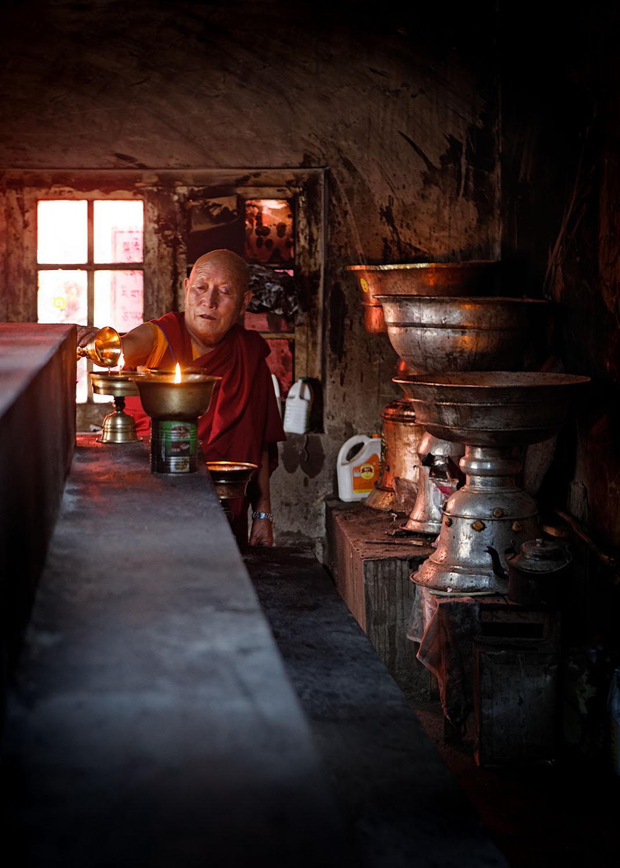 Lighting butter lamps, Hemis Monastery, Ladakh, India