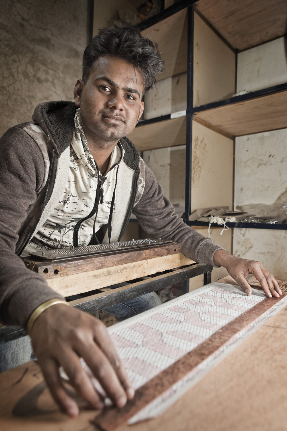 Portrait of master weaver Ganesh punching holes in the cards for the jacquard.