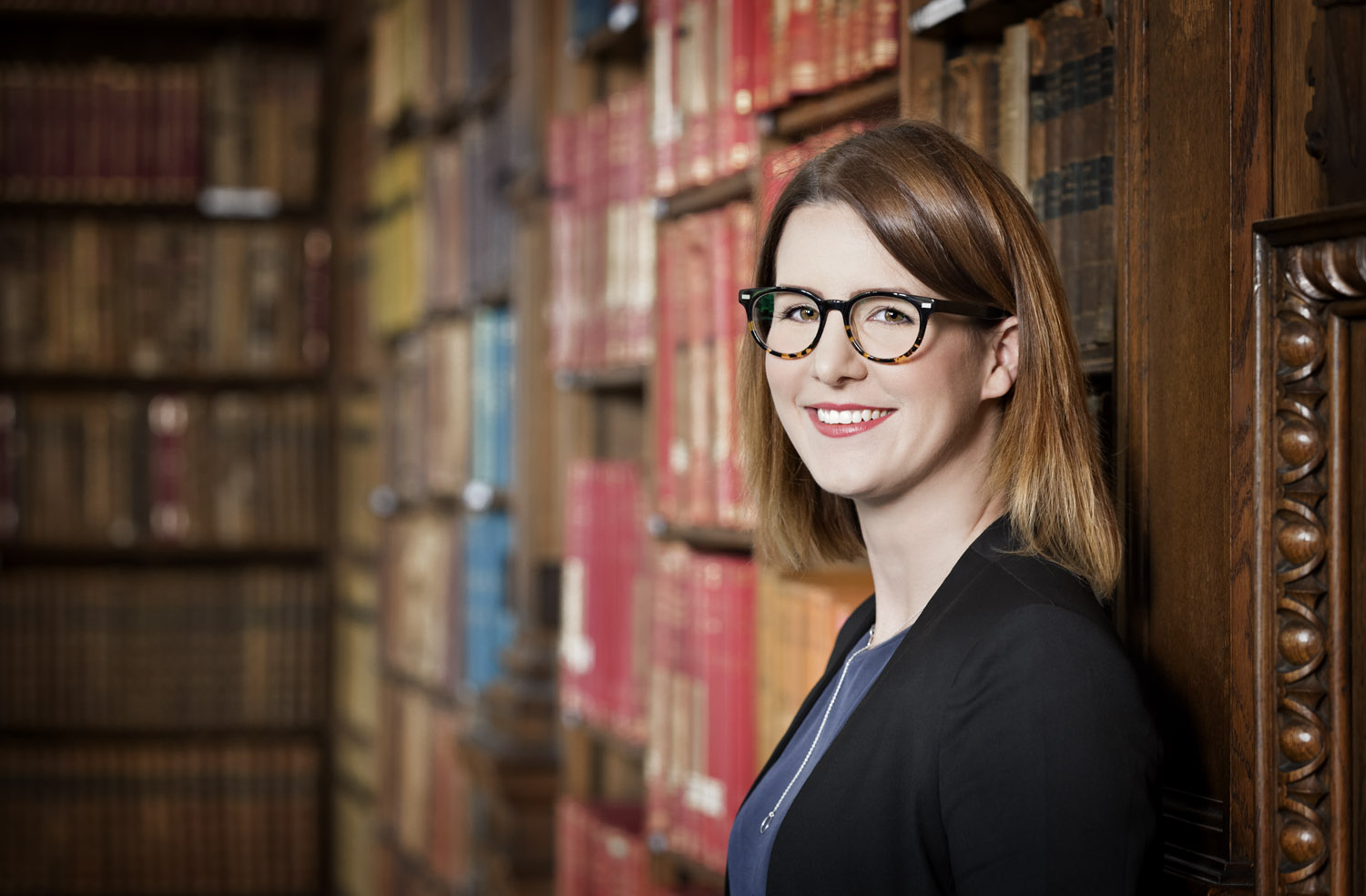 Portrait of journalist Claire Connelly in the Goodman Library at the University of Oxford Student Union, Oxford, UK
