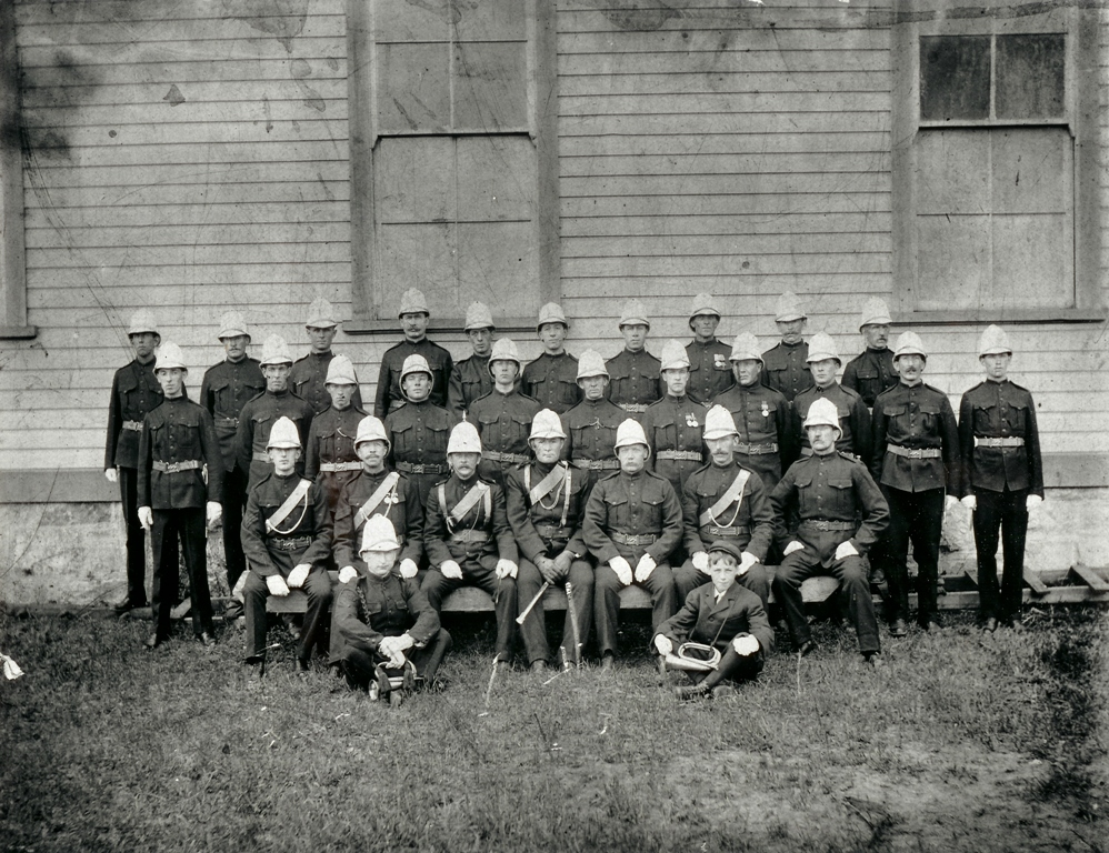 Rocky Mountain Rangers militia at Revelstoke Drill Hall, circa 1906. Robert Smith is in the bottom row (behind buglers), 4th from left. P764