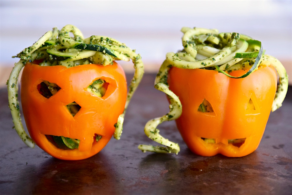 Dress up your gluten free zucchini noodles with a vegan pumpkin kale pesto. Drop them in a colorfully carved orange pepper, and you're ready for Halloween! | TastingPage.com