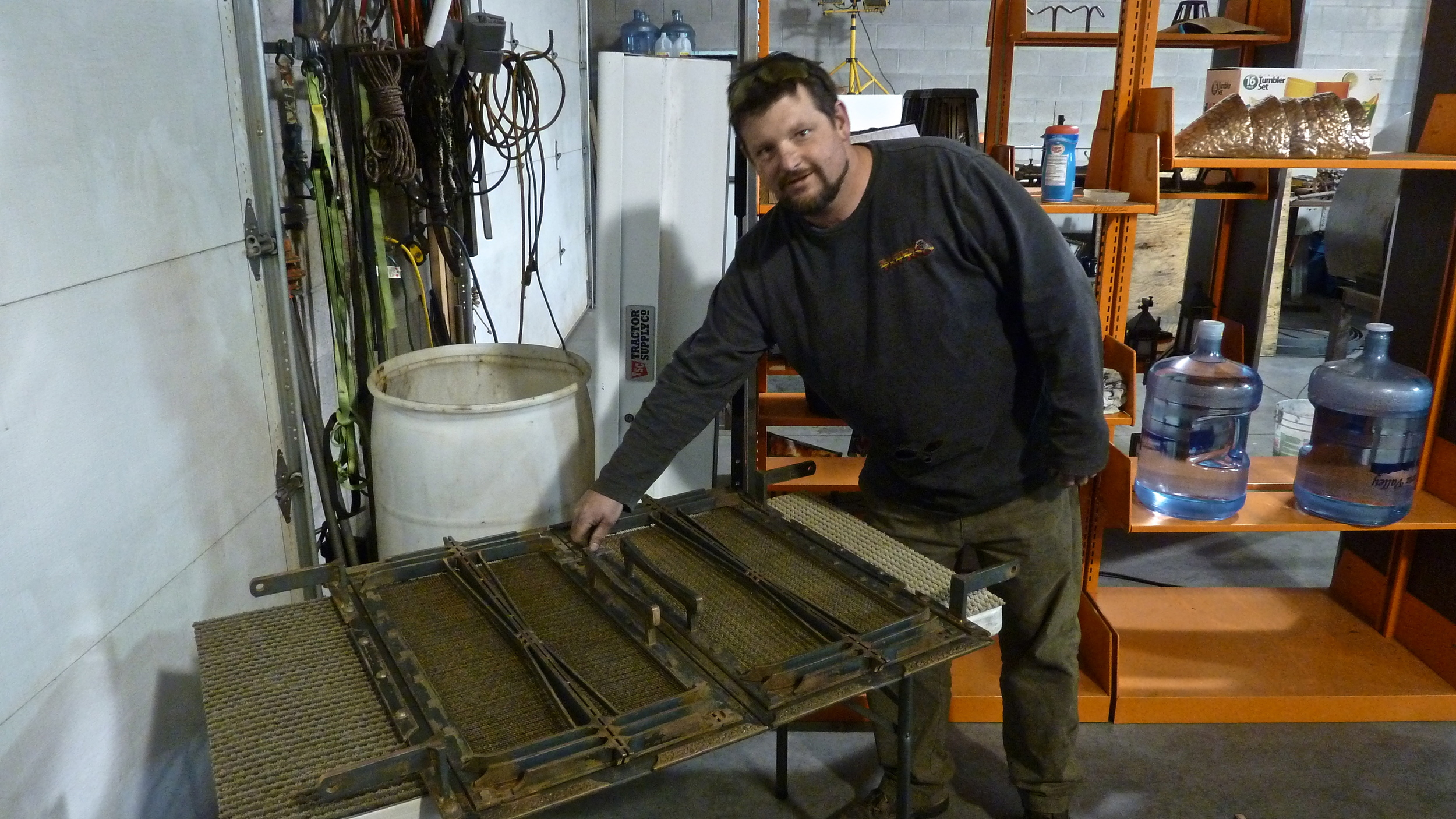 Andy showing a fireplace screen he is manufacturing for a client