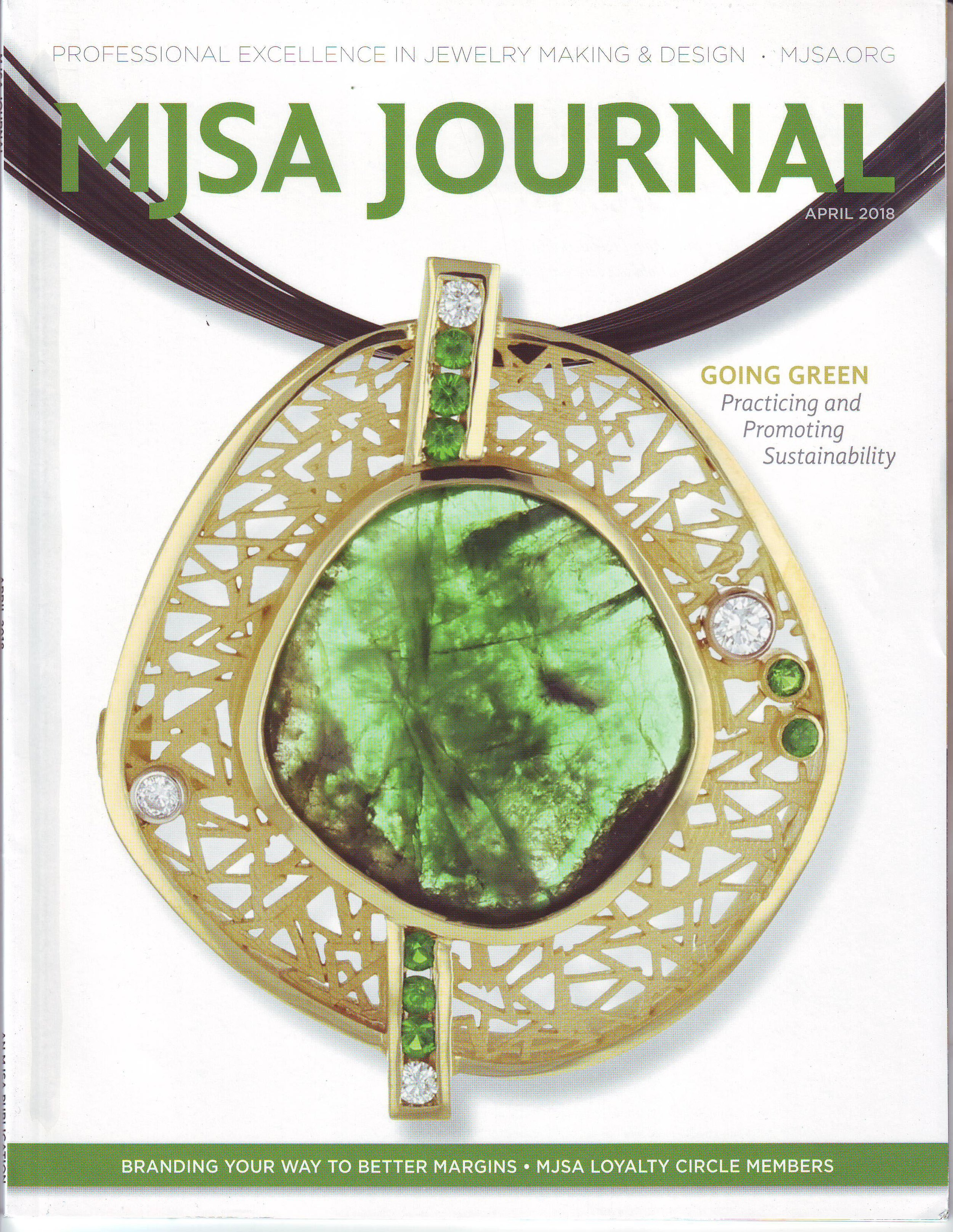 Molly Hollingsworth and Bryson Robert's emerald, tsavorite garnet, diamond and 18KY pendant featured on the cover of MJSA magazine's green practices issue.