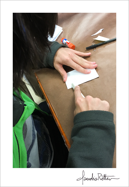 A student using a bone folder.