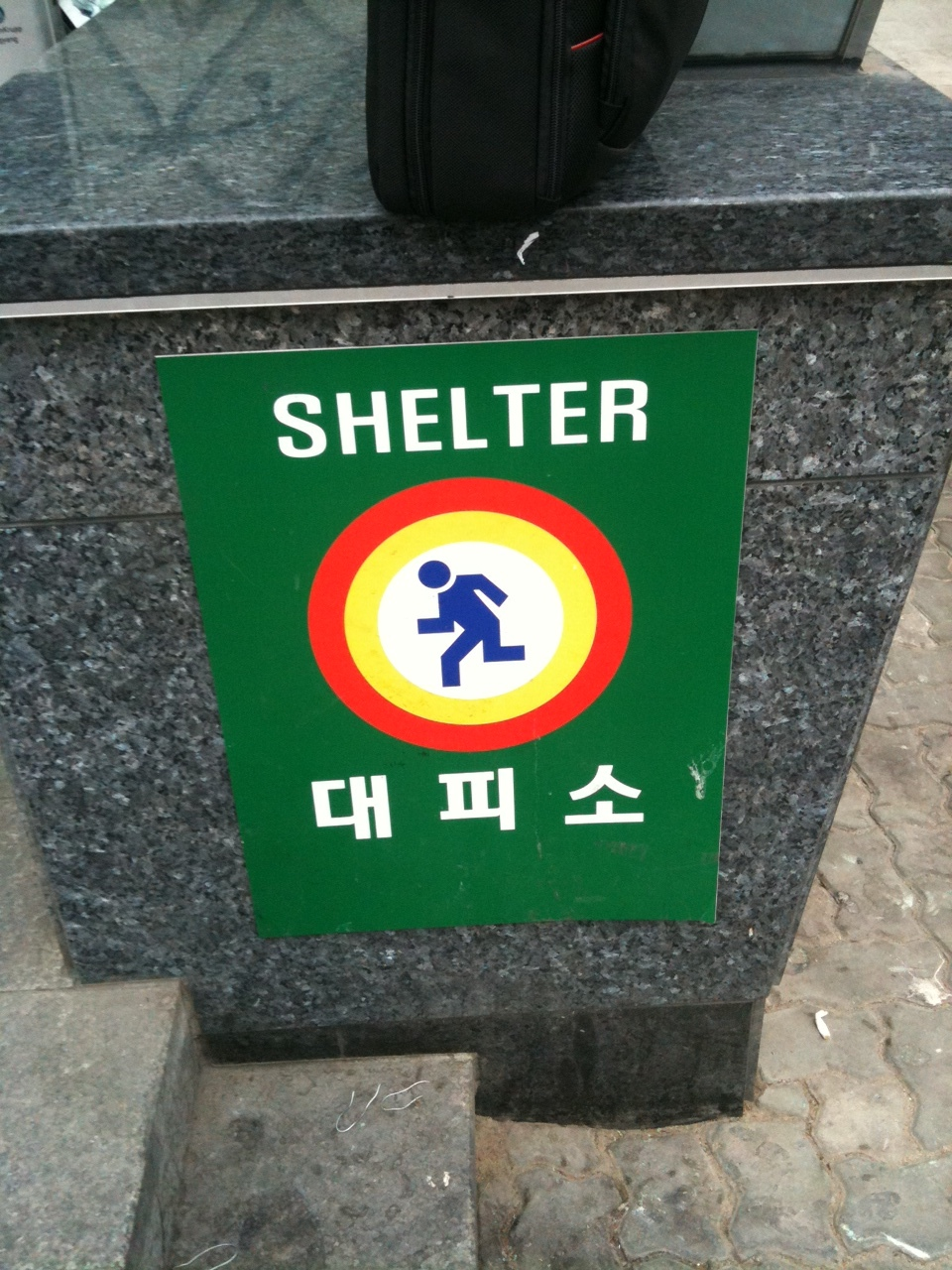 This sign is positioned outside numerous subway stations in Seoul. It's nice to know there's a shelter in case our friends in the north get a little upset.  www.presentinenglish.com    Sent from my iPhone