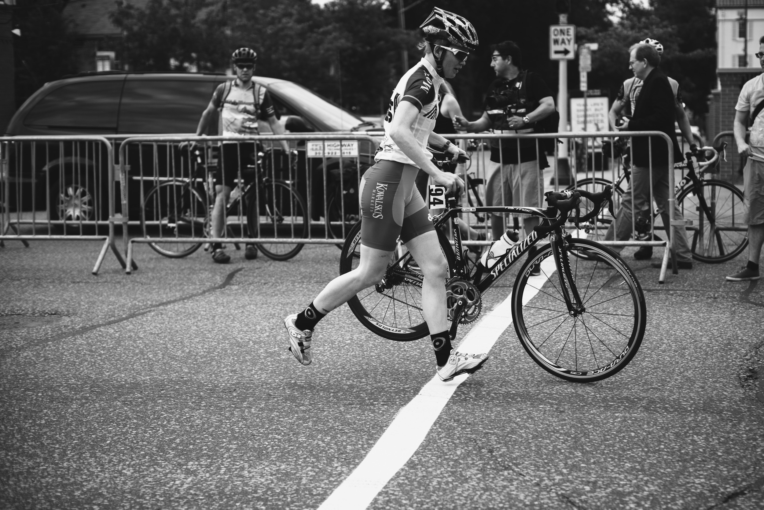 Rose Long, of theKowalski's Markets Collegiate All-Starsteam, runs her bike to the Shimano neutral support zone after a mechanical problem.