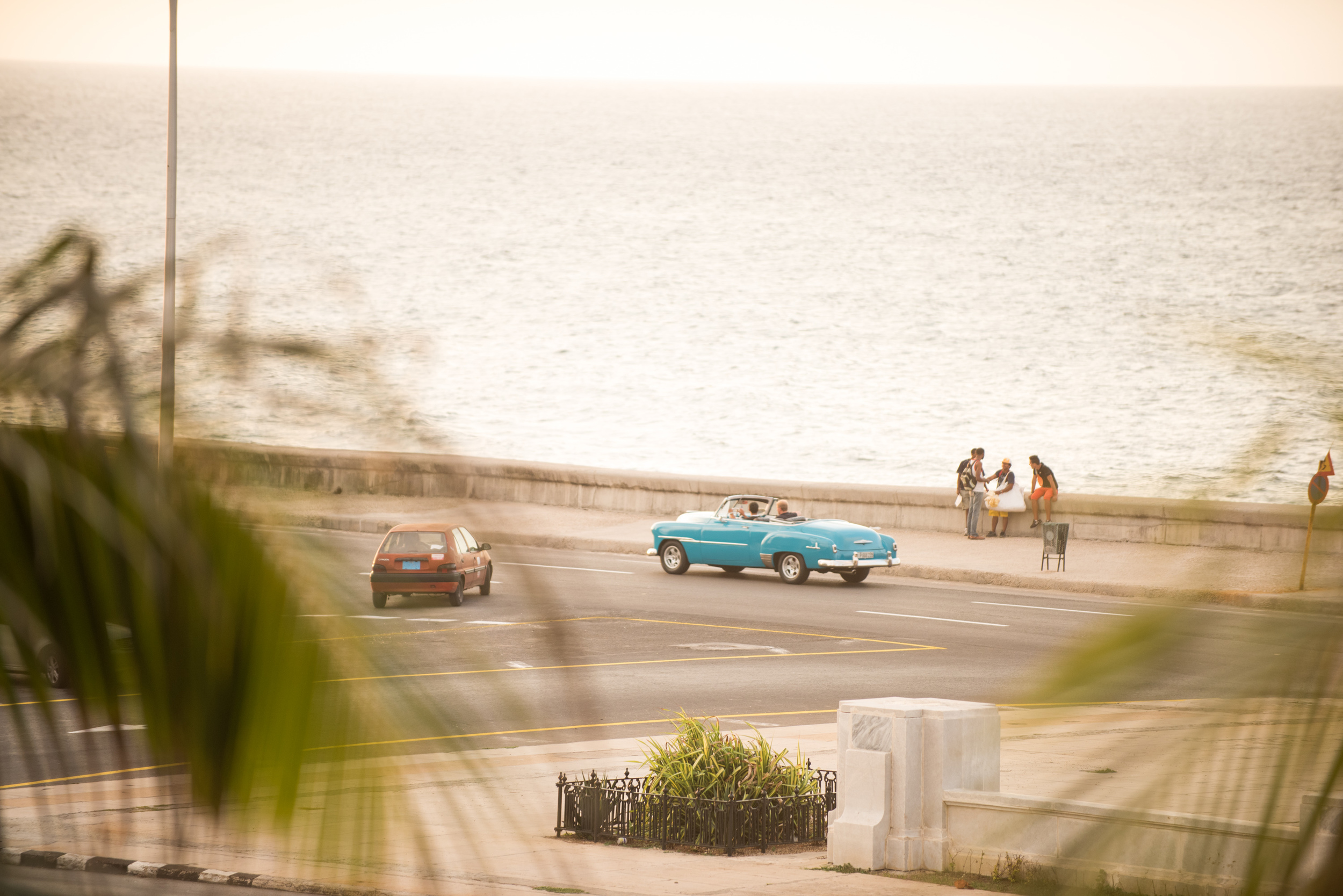 Old cars and people enjoying the evening along the Malecon – the iconic road that follows the coast through Havana.