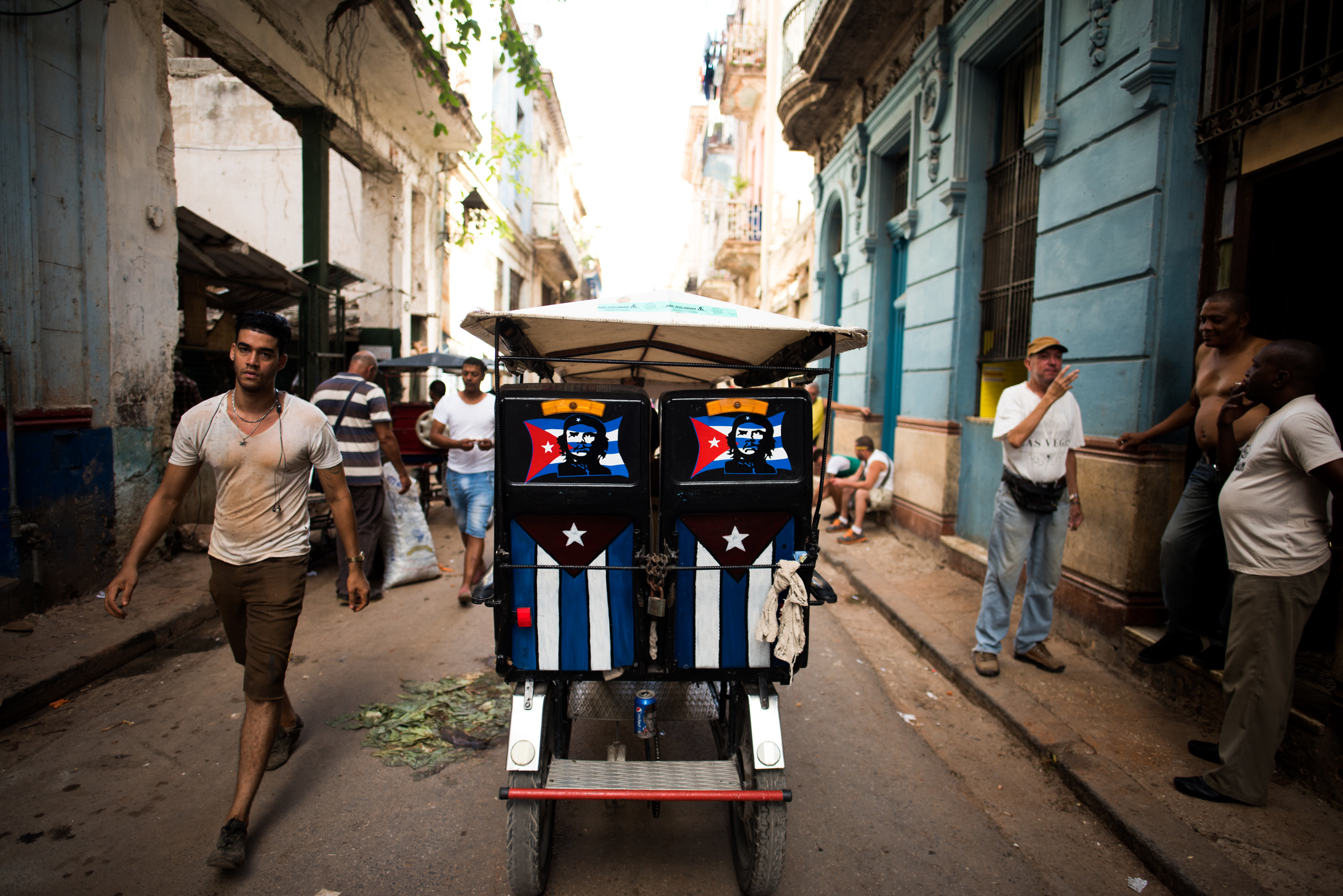 A pedicab with Cuban Flags and depictions of Che Guevara makes its way through a narrow street in Old Havana.