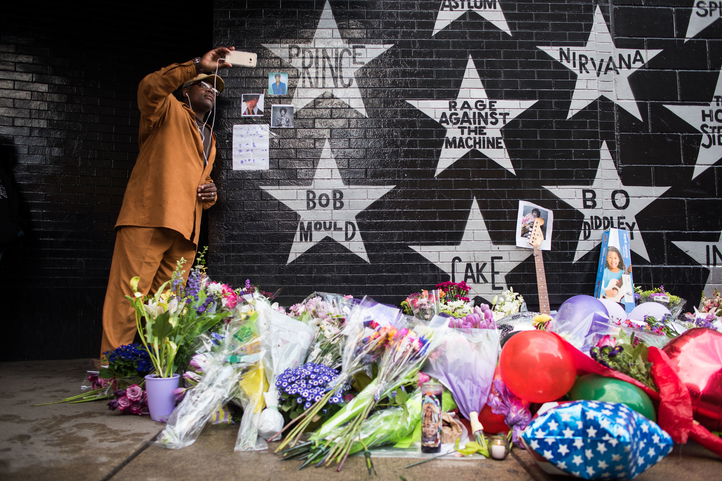 Cederic Riley takes a photo with Prince's star outside of First Ave bellow in downtown Minneapolis. April 21st, 2016.