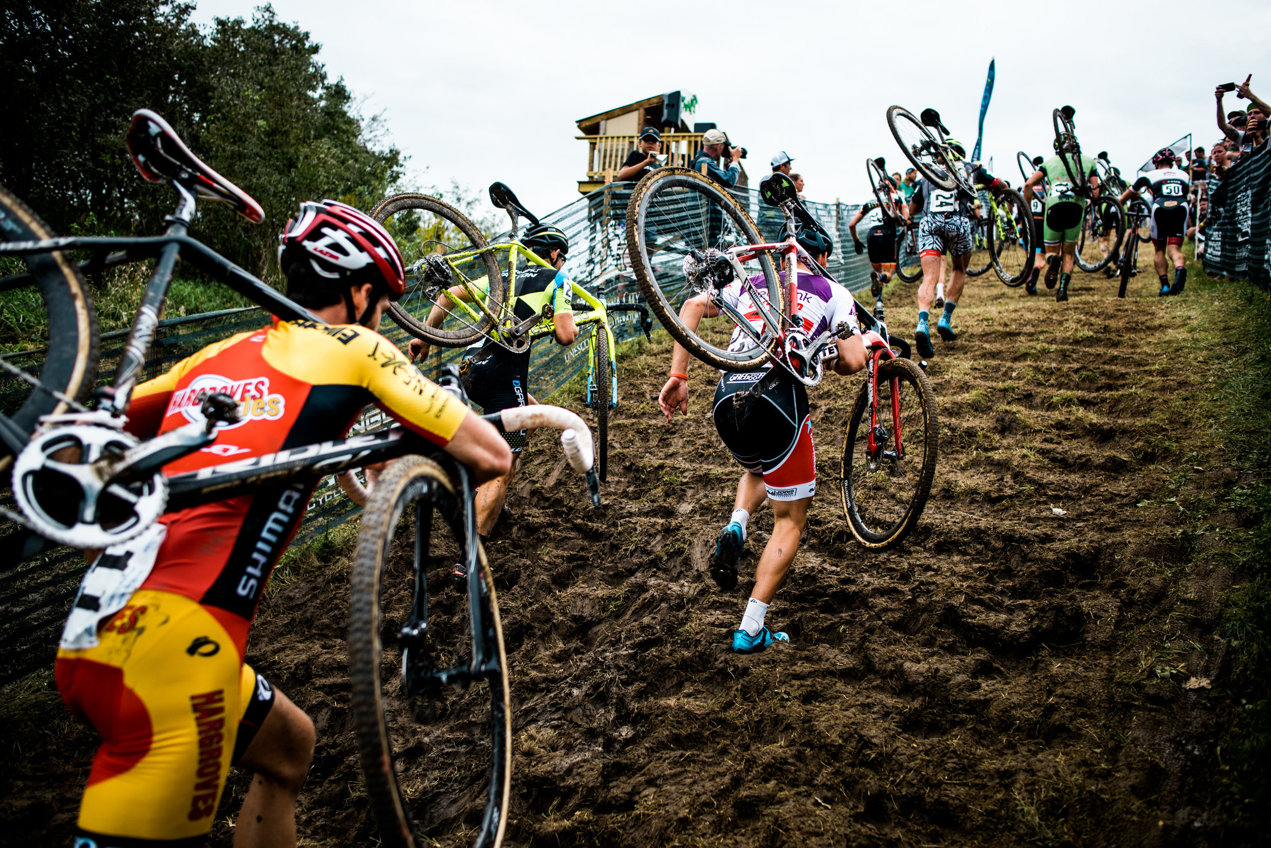 Riders run up the incredibly steep path to the summit of Mt Krumpit. Rain Friday turned the hillside into a muddy mess.