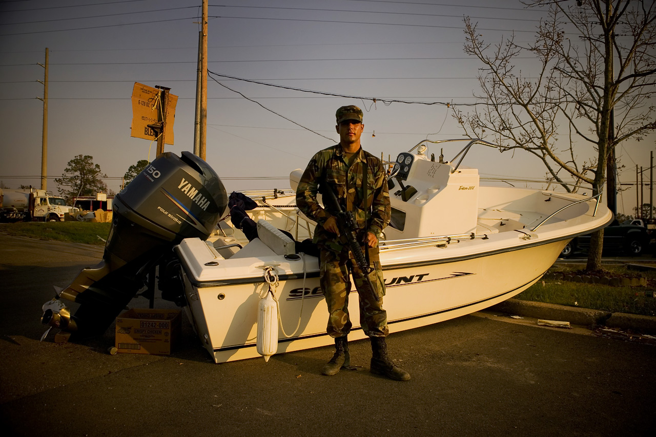 "National guardsman in front of boat, upon which is written ""Sorry about your boat it saved 5 peoples lives."" Waveland, Mississippi"