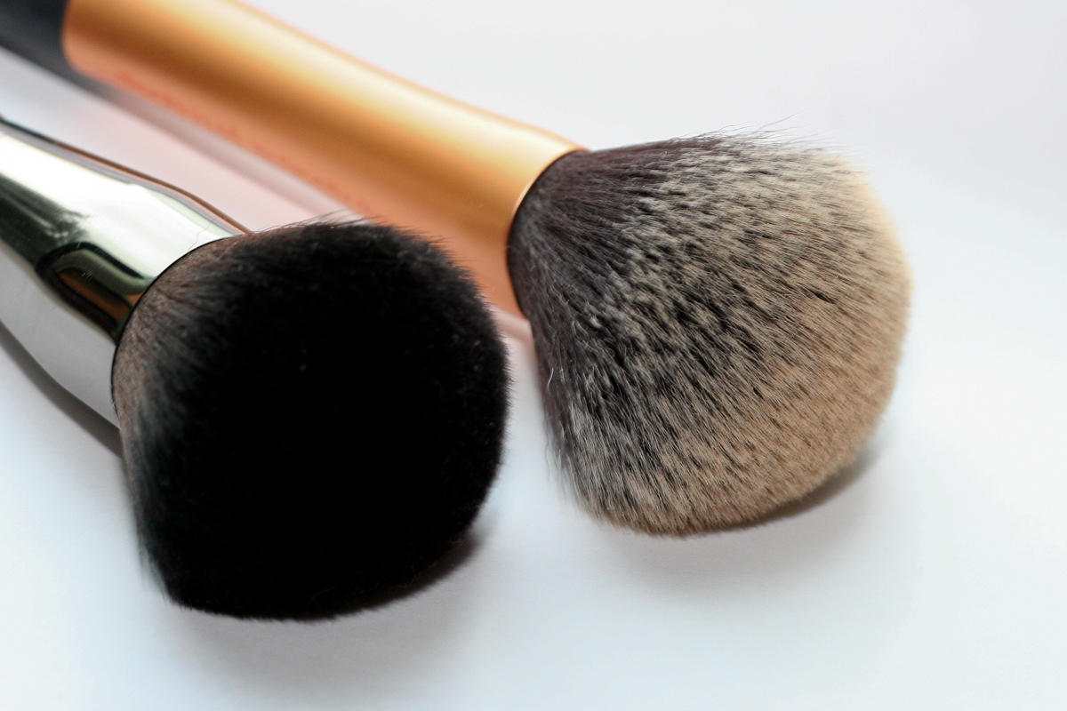 The Make Up For Ever 126 Powder Brush - Medium (left) next to my Real Techniques Powder Brush (right) for comparison. The RT brush (about $10) has a slightly shorter, thicker handle, a bigger head, and less dense bristles. It's also noticeably less soft than the MUFE brush (and that's saying something!).
