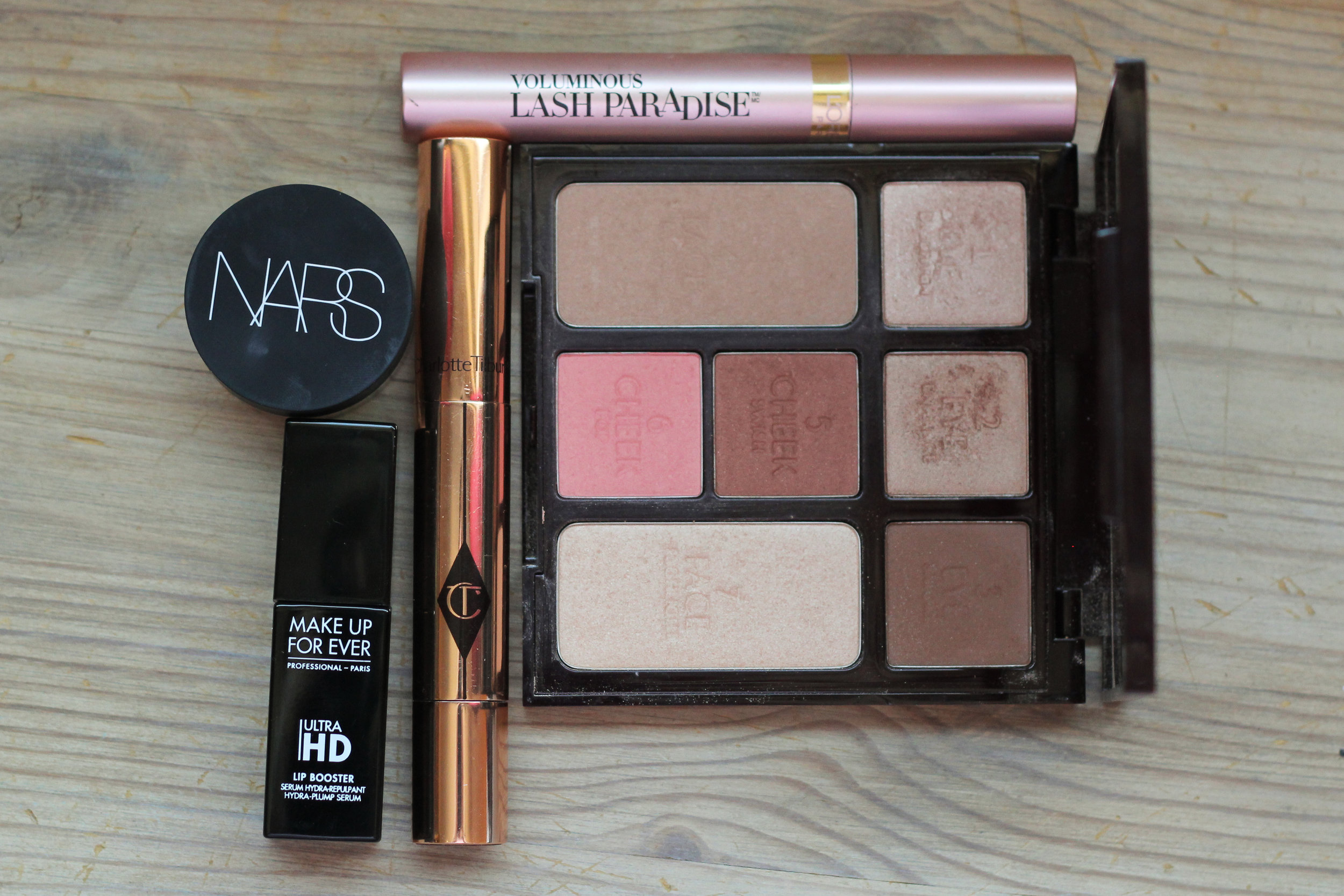 A few things I've been loving, clockwise from the bottom left: Make Up For Ever Ultra HD Lip Booster, NARS Soft Matte Complete Concealer, Charlotte Tilbury The Retoucher Pen, and Charlotte Tilbury Instant Look in a Palette - Beauty Glow.