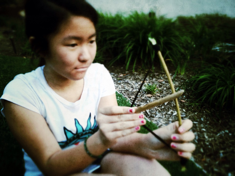 Inspired by Katniss, my girls make their own bows and arrows with twigs.