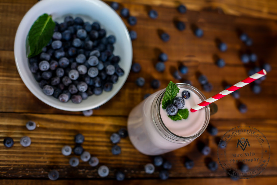 Blueberry smoothies on wooden table top view