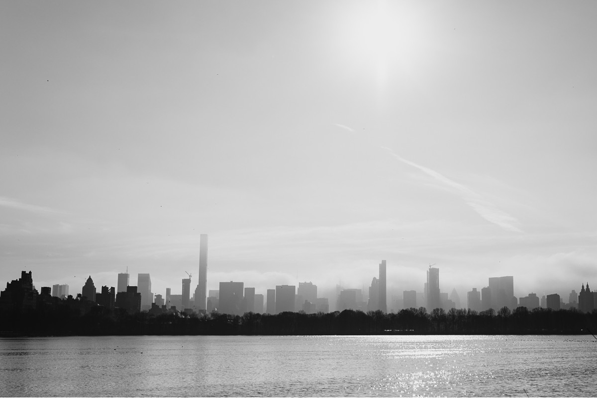 Surreal foggy New York City skyline from Central Park Reservoir.
